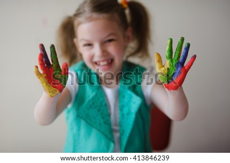 Child himself dirty in the paint and looks into the camera. Girl has fun and painting. Children's creativity. Art for baby. - stock photo