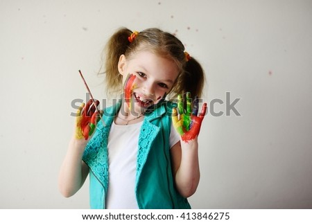 Child himself dirty in the paint and looks into the camera. Girl has fun and painting. Children's creativity. Art for baby. Dirty happy face child. Girl holding a brush in his hand - stock photo