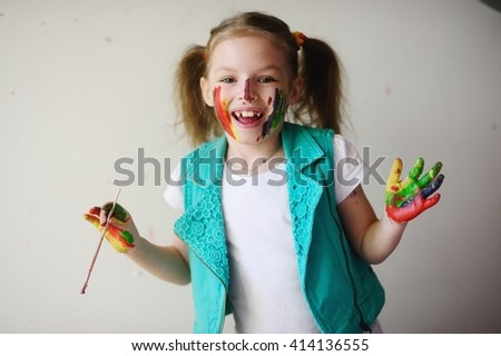 Child himself dirty in the paint and looks into the camera. Girl has fun and painting. Children's creativity. Art for baby. Dirty happy face child. - stock photo