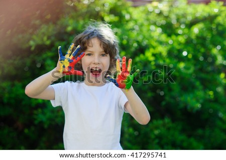 Child himself dirty in the paint and show his dirty hands ti the camera. Child has fun and painting / drawing. Children's creativity. Art for baby. Emotions. Delight. - stock photo