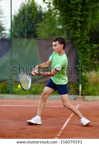 Child hitting the ball with the backhand on a dross court