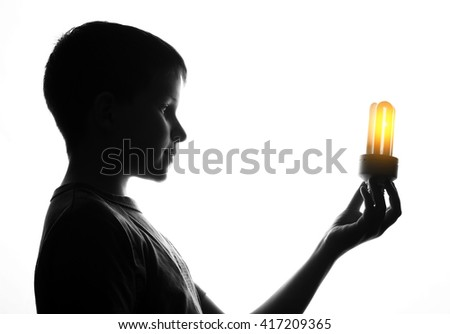 Child hold in hand energy saving light bulb