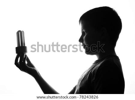 Child hold in hand energy saving light bulb - stock photo