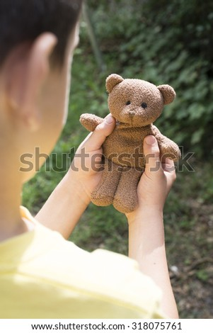 Child hold teddy in a garden.  - stock photo