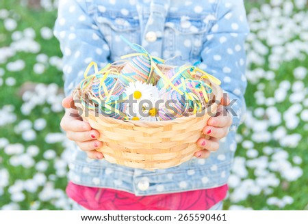 Child holding a basket with easter eggs - stock photo