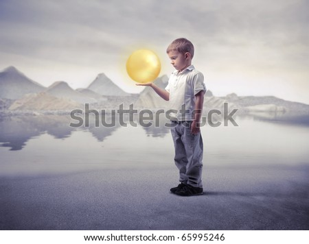 Child holding a bright sphere with lake on the background - stock photo