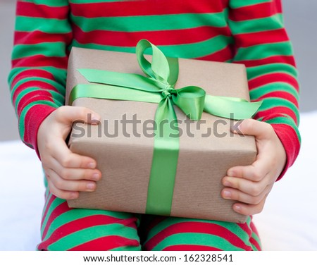 child holding a christmas present nicely wrapped - stock photo