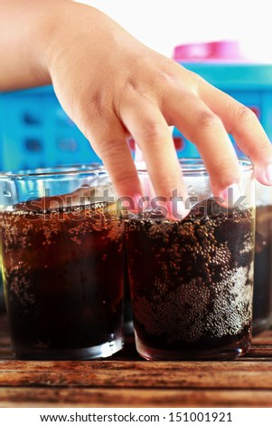 Child holding a glass of cola with ice. - stock photo