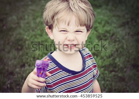 Child holding a gun being tough