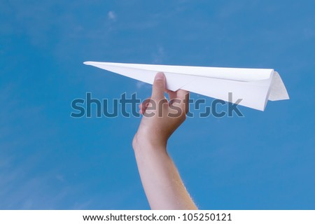 child holding a paper airplane against a blue sky - stock photo