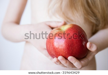 Child holding a red apple, closeup shot