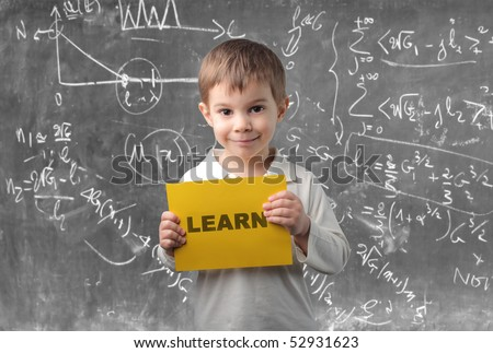 Child holding a sheet with learn written on it - stock photo