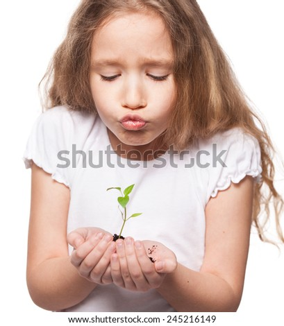 Child holding a sleedling. Girl with sprout - stock photo