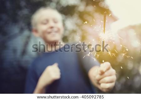 Child holding a sparkler, blurred shallow focus image, focus on sparks, Instagram toned image - stock photo