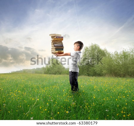 Child holding a stack of books on a green meadow - stock photo