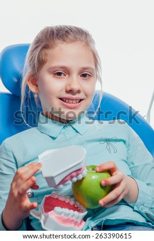 child holding a teeth sample and apple - stock photo