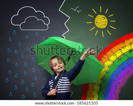 Child holding an umbrella standing in front of a chalk drawing of changing weather from rain storm to sun shine with a rainbow on a school blackboard - stock photo