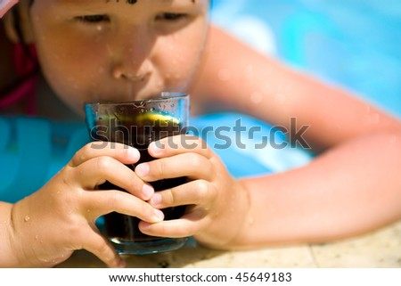 Child holding cola drink focus on glass and fingers - stock photo