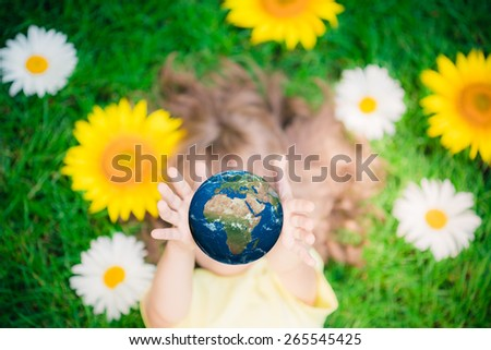 Child holding 3D planet in hands against green spring background. Earth day holiday concept. Elements of this image furnished by NASA - stock photo