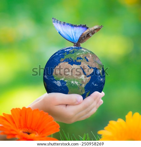 Child holding Earth planet with blue butterfly in hands against green blurred background. Earth day. Spring holiday concept. Elements of this image furnished by NASA - stock photo