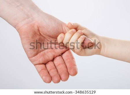 Child holding father's thumb finger, closeup shot on grey background - stock photo
