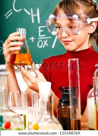 Child holding flask in chemistry class. - stock photo