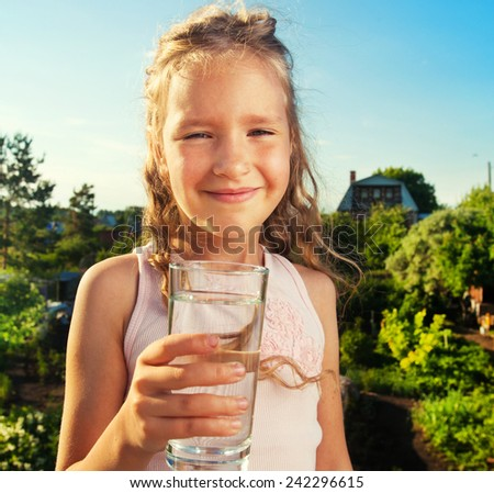 Child holding glass water. Girl at summer - stock photo