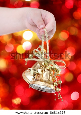 Child holding golden Christmas tree decorations on lights background - stock photo
