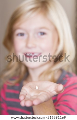 Child holding her missing front tooth