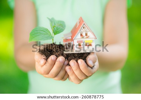 Child holding house and tree in hands against spring green background. Real estate concept - stock photo