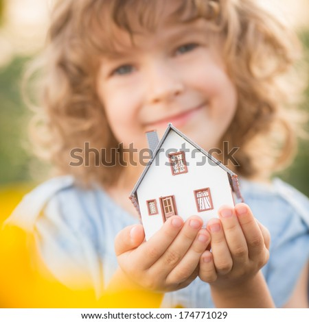 Child holding house in hands against sunflower field background. Real estate concept - stock photo