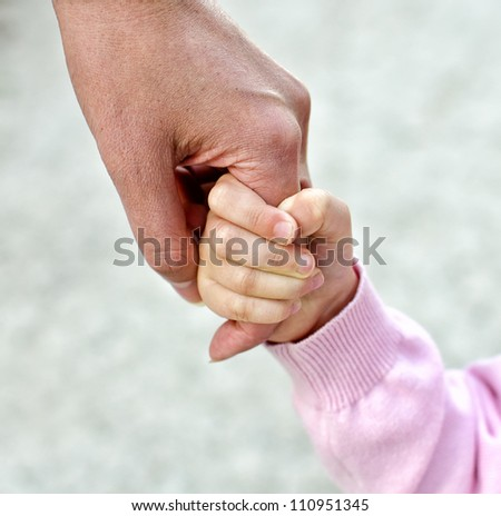 Child holding mother's hand - stock photo