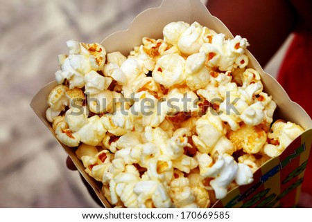 Child holding popcorn a caramel coated - stock photo