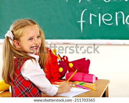 Child holding school cone in classroom. - stock photo