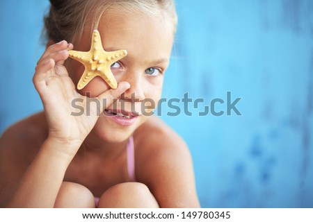 Child holding seashell on blue background - stock photo