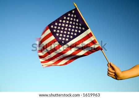 Child holding small US flag on the wind outdoor. - stock photo