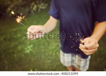 Child holding sparklers, shallow focus, focused on sparks - stock photo