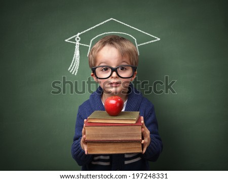 Child holding stack of books with mortar board chalk drawing on blackboard concept for university education and future aspirations - stock photo