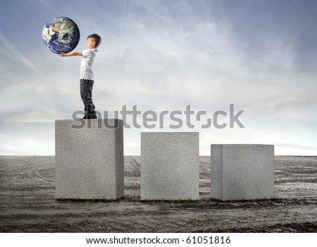 Child holding the earth and standing on the highest of three cubes on a field - stock photo