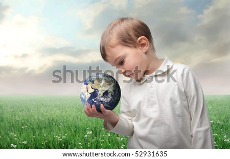 Child holding the earth in his hand with countryside on the background - stock photo