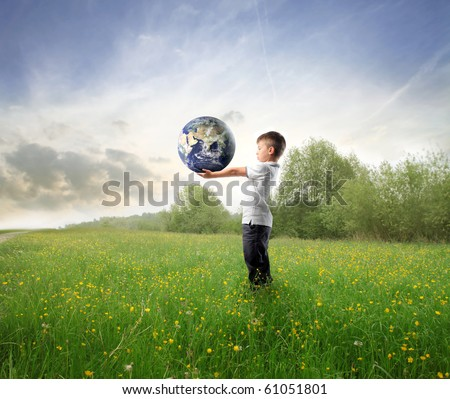 Child holding the earth on a green meadow - stock photo