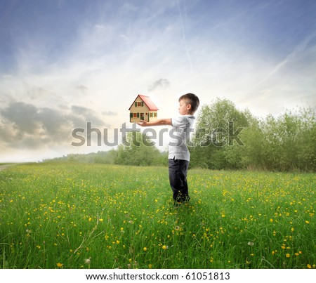 Child holding the model of a house on a green meadow - stock photo