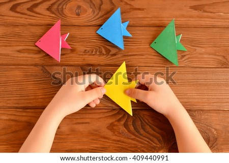 Child holds a origami fish in his hands. Set of colorful origami fish on a wooden table  - stock photo
