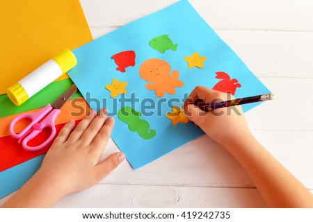 Child holds a pencil and draws. Child doing a card with sea animals and fish. Sheets of colored paper, scissors, glue, set for kids art  - stock photo