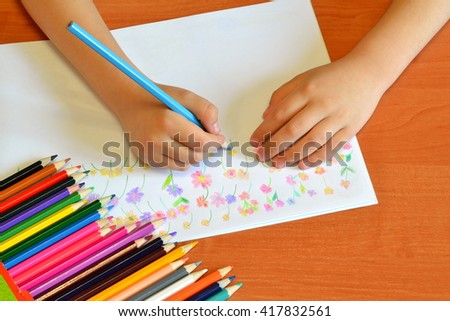 Child holds a pencil in hand and draws flowers. Sketchbook and set of colored pencils. Art class in kindergarten  - stock photo