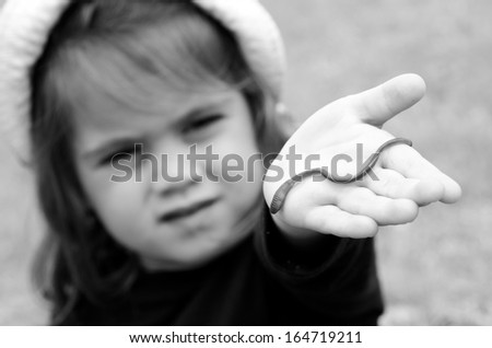 Child holds a worm on here hand.