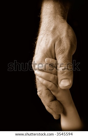 Child holds grandfather's weathered hand (sepia)