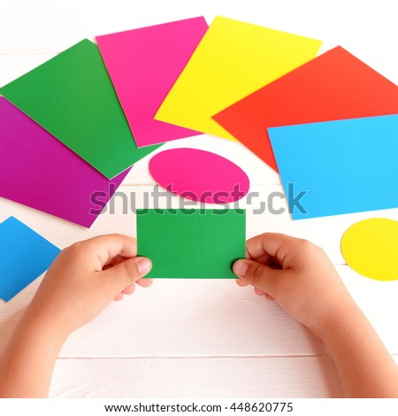 Child holds green cardboard rectangle in hands and looking for corresponding color card. Kid learns colors and form with paper cards. Concept development in preschool children in kindergarten, at home - stock photo