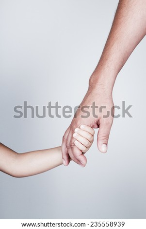 Child holds the hand of father - stock photo