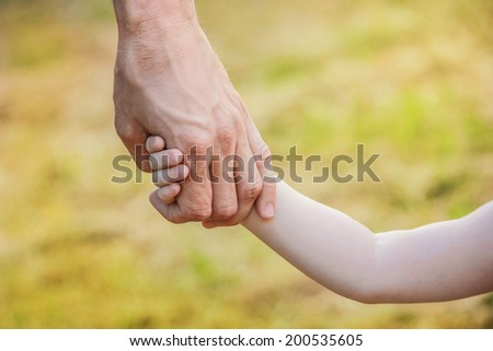 Child holds the hand of his father - stock photo